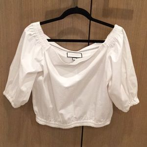 Ivory colored, off the shoulders blouse.